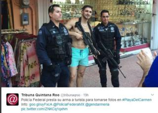 A photo tweeted by news site Tribuna Quintana Roo shows a tourist with a weapon posing with two Mexican federal police officers