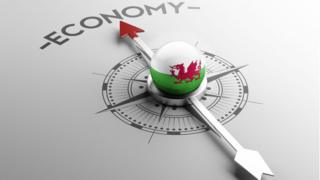A compass with a Welsh flag in the middle, with the needle pointing to the word economy