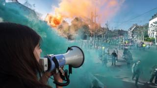 A protester speaks through a megaphone as smoke from coloured smoke bombs billows near people taking part in the annual May Day rally in Strasbourg