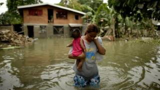 Levelyn Alcoriza leaves her submerged house in Macapagal, north of Manila, on Wednesday, after a typhoon hit the area earlier in the week
