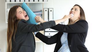 Dos mujeres peleando en la oficina.