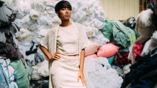 A fashion model poses in a room of textile offcuts in Cambodia