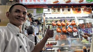 Singaporean chef Chan Hong Meng in front of his Michelin-starred chicken rice and noodle stall