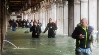 Tourists walk through flooded St Mark Square in Venice on 29 October 2018
