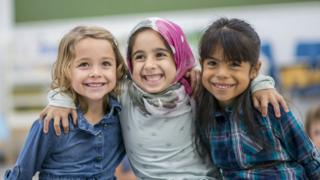 Girls smiling - one white, one in a hijab, one Asian
