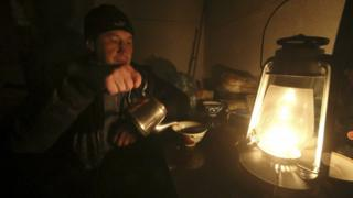 A Crimean Tatar uses a burning oil lamp due to a power cut inside his house in the village of Strogonovka, Simferopol district, Crimea, 26 Nov
