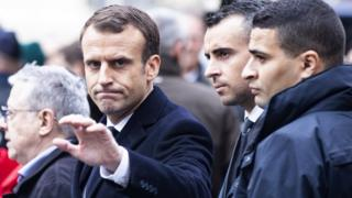 Mr Macron inspecting the damage in Paris caused by the protests.