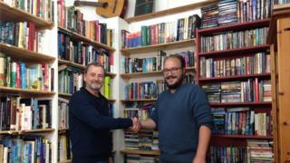 Paul Morris (left) and Ceisjan Van Heerden shake hands in a book shop