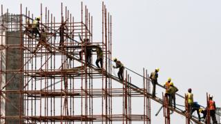 in_pictures Construction workers stand on scaffolding in Abuja, Nigeria - Thursday 12 March 2020