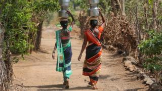 Women carry pitchers after filling them with water from a hand pump to their houses in Thane district in the western state of Maharashtra, India, May 30, 2019