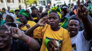 Supporters of the ANC and South Africa's new President Cyril Ramaphosa sing and dance after his swearing in outside the South African general assembly on 15 February 2018 in Cape Town