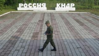 "A guard walks along a platform past signs, which read ""Russia"" (L) and ""DPRK""(Democratic People""s Republic of Korea), at the border crossing between Russia and North Korea in the settlement of Tumangan, North Korea July 18, 2014"