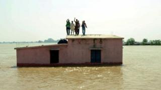 Flood affected people stand on the roof of a submerged house as they wait to be rescued at Kasimpurchak, near Danapur Diara in Patna in eastern Bihar state.