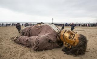 A giant puppet is seen on the beach surrounded by people looking on