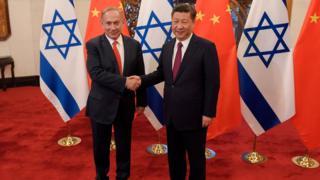 El primer ministro israelí, Benjamin Netanyahu; y el presidente de China, Xi Jinping, se dan la mano.