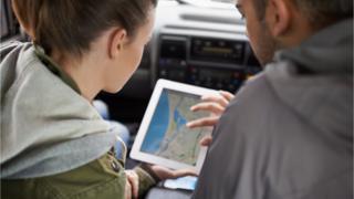 Homem e mulher olham um mapa na tela de um tablet