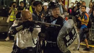 香港 新界 葵涌 警署 外 一名 警署 警長 (左) 舉起 雷鳴 登 霰彈槍 指向 示威 者 / 30/7/2019)