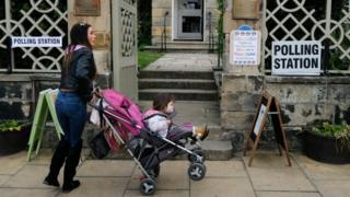 A woman at a polling station with her toddler