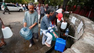 Moradores enchem recipiente com água