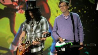 "Saul Hudson, ""Slash"", de la banda Gun's and Roses (izquierda) y Bill Gates con una guitarra. (Foto: David Paul Morris)"