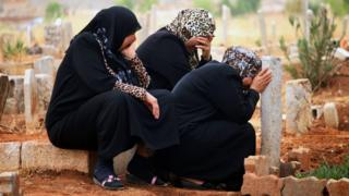 People pray near relatives' graves during Eid al-Fitr in the rebel-held town of Dael, Syria (6 July 2016)