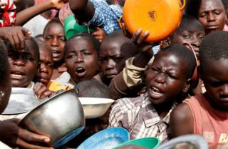 Internally displaced people wait for food distribution.
