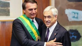 Bolsonaro cumprimenta Piñera em sua posse, onde aparece com faixa presidencial