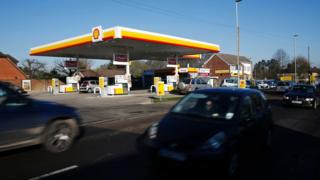 Cars drive past a Shell garage in the UK