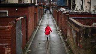 A young girl plays in an an alleyway in the Gorton area of Manchester
