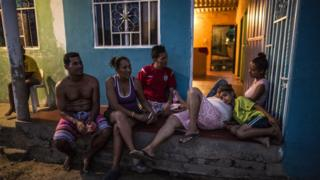 Stephanie, Diego and others sit and chat outside their front gate