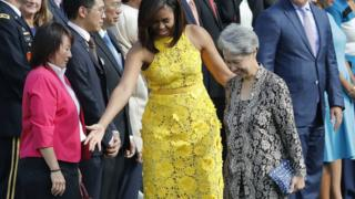 "First lady Michelle Obama directs Ho Ching, right, wife of Singapore""s Prime Minister Lee Hsien Loong, where to stand during a state arrival ceremony on the South Lawn of the White House in Washington, Tuesday, Aug. 2, 2016"