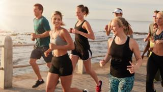 Healthy young people running along a seaside promenade