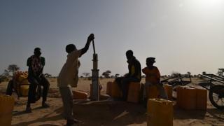 children dey try pump wata from borehole.