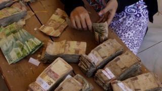 Warga menghitung uang lusuh yang akan ditukarkan dengan uang baru,saat digelar Ekspedisi Kas Keliling Pulau Terluar, Terdepan dan Tertinggal (3T), di desa Tamher Timur, Pulau Kesui, Maluku, Jumat (2/11/2018).