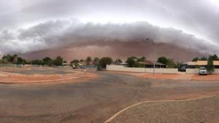 A storm creates a wall of dust above Port Hedland in Western Australia