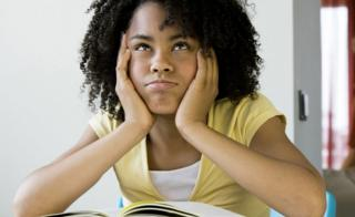 A girl with an afro seated a desk with a book
