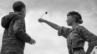 A girl in cadet gear and a boy looking on watch her conker flying in the air.
