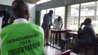 Un observateur regarde les électeurs défiler devant les membres de la CEI.