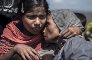 Una niña consuela a su madre en la orilla del río Naf. Han llegado a Bangladesh escapando del ejército de Myanmar.
