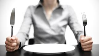 Mujer sentada frente a un plato vacío y empuñando un cuchillo y un tenedor
