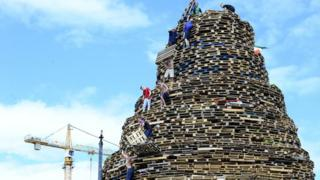 Final preparation takes place for the bonfire on Sandy Row in Belfast in July 2017
