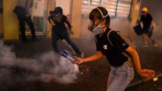 香港 九龍 深水埗 一名 女 示威 者 躲避 防暴 警員 發射 的 催淚彈 / 14/8/2019)