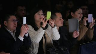 Chinese people take photos with iPhone and iPad during Bosideng Down Wear Collection on the third day of Mercedes-Benz China Fashion Week Autumn/Winter 2013/2014 at 751 D.PARK Workshop on March 26, 2013 in Beijing, China.