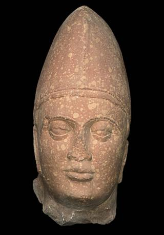 A sculpture of a Kushan king made of spotted red sandstone