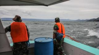 An Indonesian search-and-rescue team looks for victims of a sunken ferry on Lake Toba in Indonesia, 19 June 2018