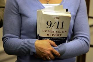 Carie Lemack, who lost her mother Judy Larocque in the 9/11 World Trade Center attack, holds a copy of the 9/11 Commision Report during a press conference November 30, 2004