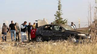 Turkish police forensic experts examine a car after a blast by two militants in Haymana, near Ankara (8 Oct)