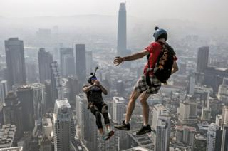 Two base jumpers jump off the edge of a tall building