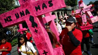 """Women carry pink crosses during the """"Day without women"""" protest in Mexico"""