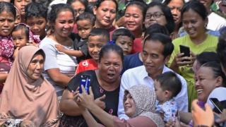 Capres petahana Joko Widodo menyapa warga sebelum menyampaikan pidato kemenangannya sebagai Presiden Republik Indonesia periode 2019-2024 di Kampung Deret, Tanah Tinggi, Johar Baru, Jakarta Pusat, Selasa (21/5/2019).
